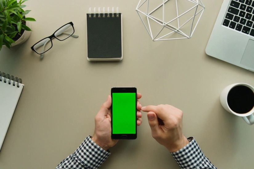 Man using smartphone with green screen on office desk background. Male  hands tapping on touchscreen, swiping, scrolling pages on cell phone. Tip  view.