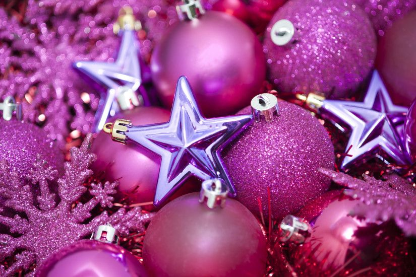 a festive holiday background with pink coloured glittery christmas tree  ornaments on a bed of sparkling