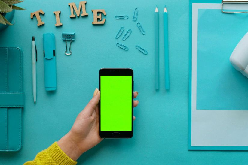 Woman using smart phone with green screen on blue desk background with blue  details. Female hands scrolling pages/ Green touchscreen. Chroma key.