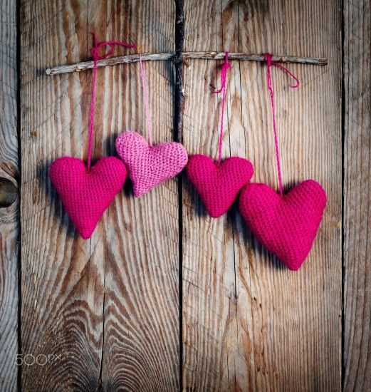 Crochet pink hearts on wooden background. - Crochet pink hearts on wooden  background. Toned