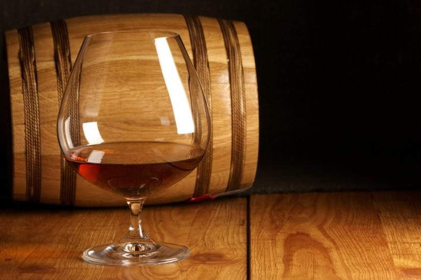 Glass of wine on the background of a wooden wine barrel