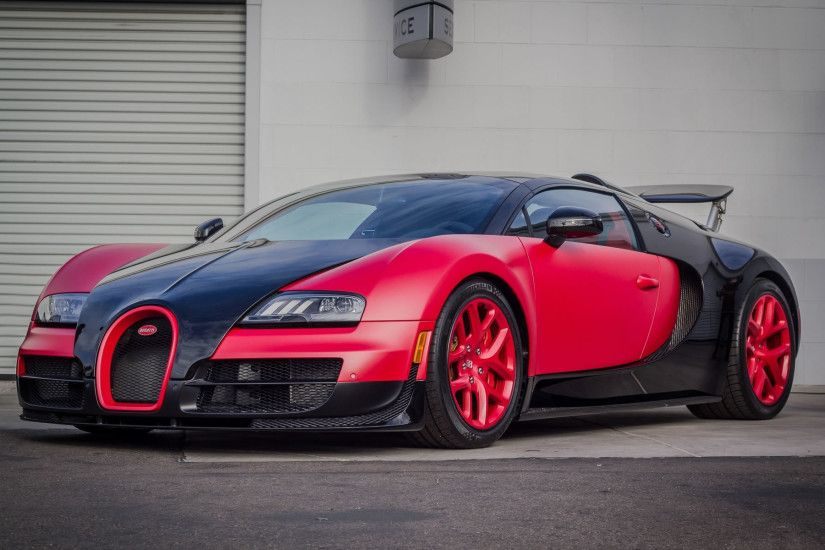 Red and black Bugatti Veyron Super Sport in grey wall