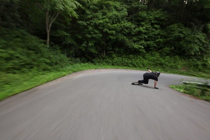 Longboarder Flies down Winding Road in Forest