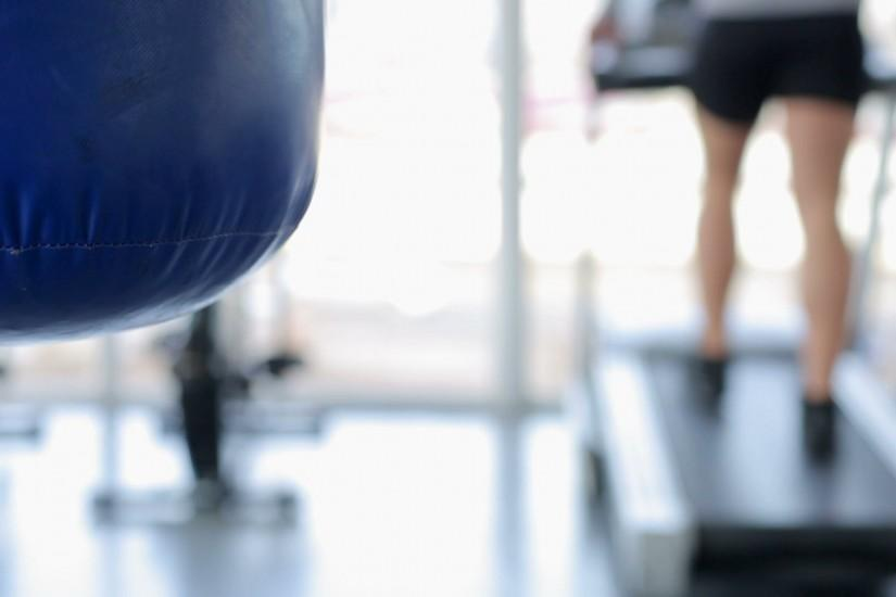 Defocused man walking on treadmill, punching bag hanging in gym, background  shot. Stock Footage