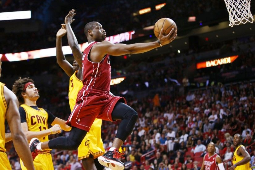 Miami Heat's Dwyane Wade slides past Cleveland Cavaliers' Anthony Bennett  and Anderson Varejao for two points during the first half of an NBA  basketball ...