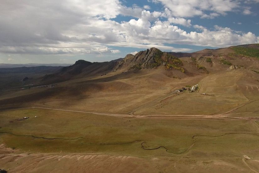 Park Terelj steppe near Ulaanbaatar Mongolia. Summer autumn sunny blue sky  clouds. Beautiful Mongolian nature. Aerial drone helicopter flight forward  high ...