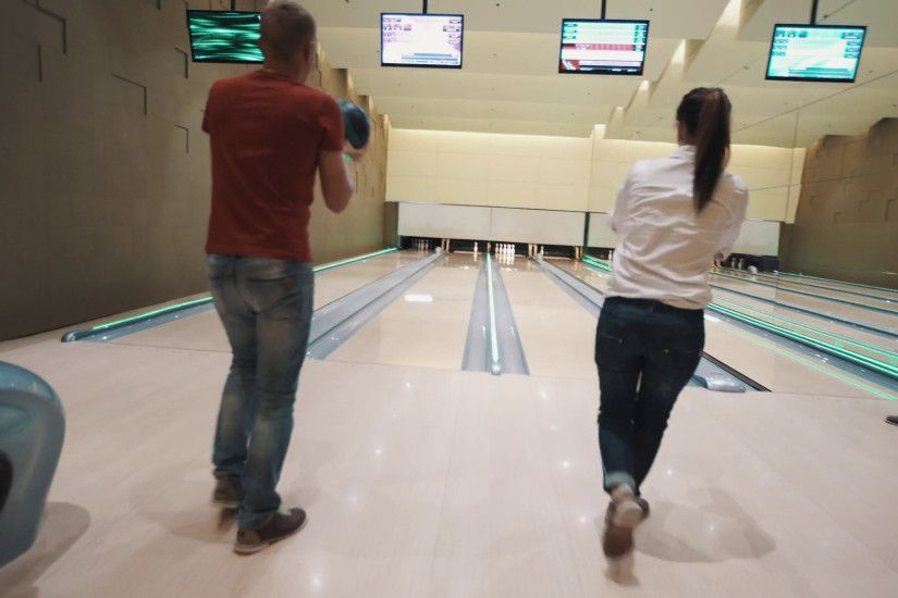 Man and girl throws bowling balls simultaneously in bright skittle ground  with large wall mirror, flashing colorful lights Stock Video Footage -  VideoBlocks