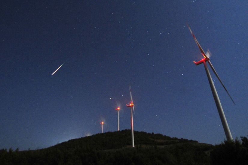 PHOTO: A meteor streaks across the sky during the Perseid meteor shower at  a windmill farm near Bogdanci, Macedonia, in the early morning of Aug. 13,  2014.