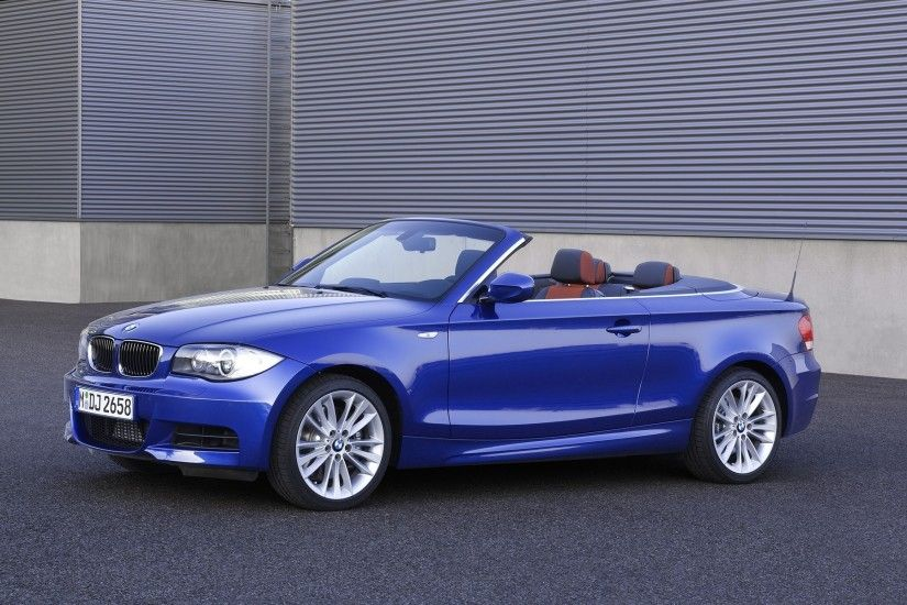 Beautiful blue BMW 135i with the top down the wall