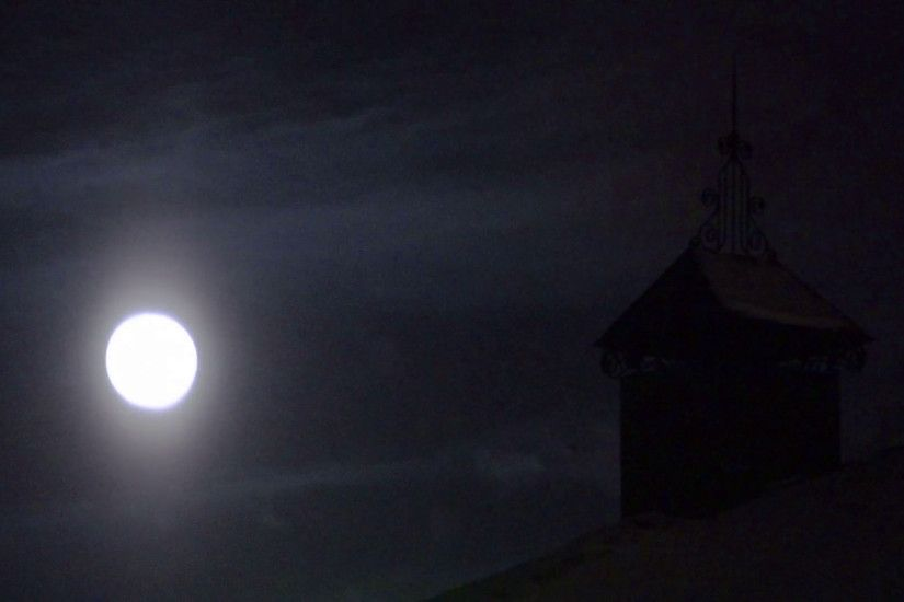 The full moon in the night sky, in the background the chimney of the house.  for a creepy effect Stock Video Footage - VideoBlocks