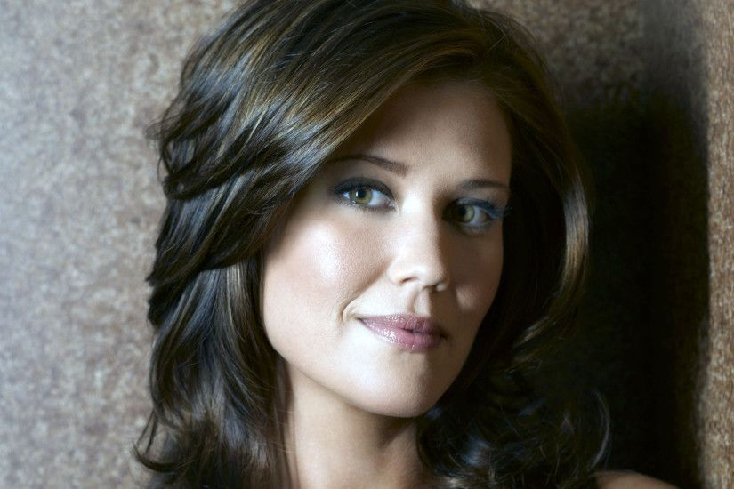 Sarah Lancaster against a stone wall wallpaper