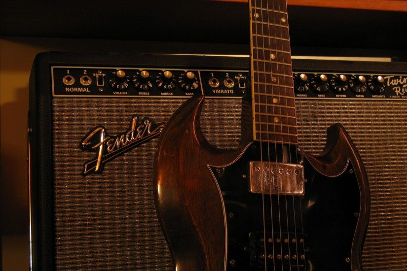 black fender guitar amplifier and brown sg electric guitar
