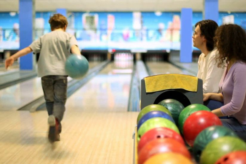 Parents sit and watch little boy throws bowling ball to beat skittles Stock  Video Footage - VideoBlocks