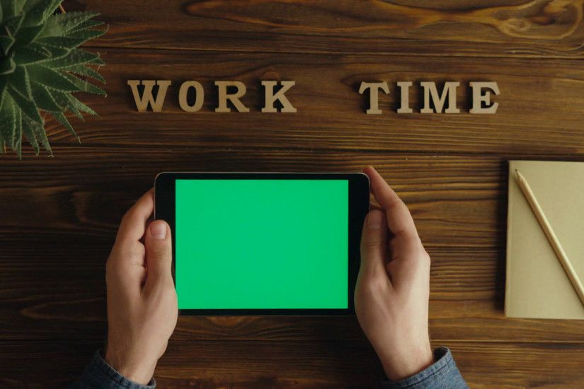 videoblocks-business-man-using-black-tablet-device-with-green-screen-hands-scrolling-checking-information-on-tablet-with-green-screen-top-view-office- desk- ...