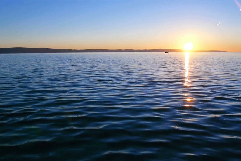 Peaceful scene of sunset on calm blue sea with fishermans in background  Stock Video Footage - VideoBlocks