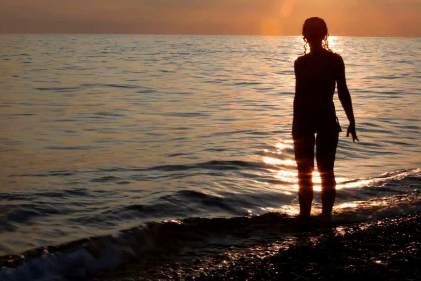 silhouette of young woman on beach, sunset sky and sea in background Stock  Video Footage - VideoBlocks