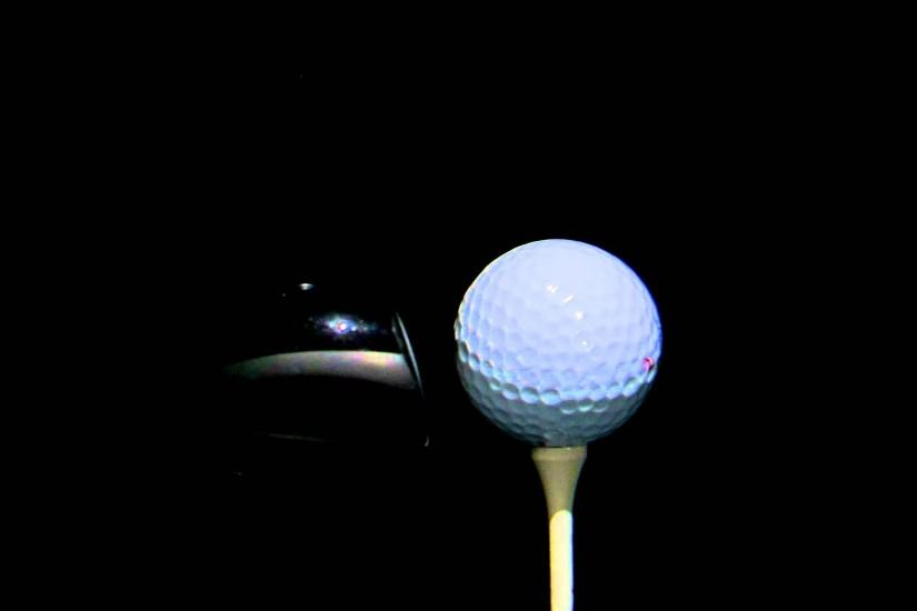 Close up of a golf ball being hit on a black background.