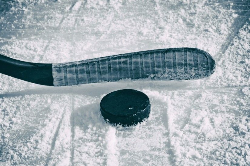 Hockey stick and puck on the ice wallpaper
