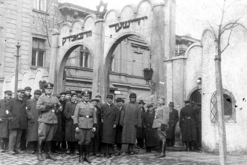German Order Police and Jewish residents of the Krakow Ghetto are  photographed in front of the ghetto gate. The purpose of the photo is  unclear, al…