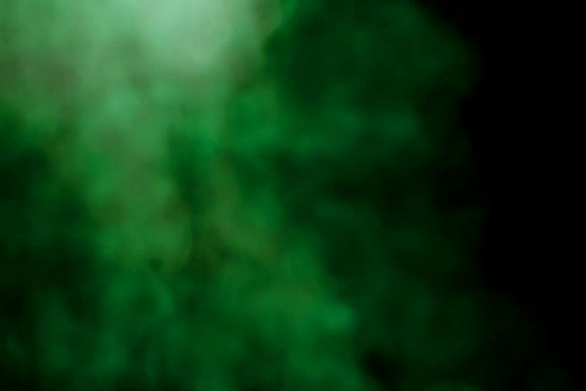 Smoke colorful green on black background. Abstract smoke background, green  colored steam shapes rising like clouds from a volcano. Studio shot.