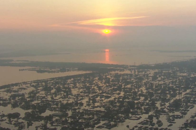 Hurricane Katrina Flood Damage. Hurricane Katrina causes severe damage to  New Orleans. Homes are submerged in water. The sun rises over the  destruction.