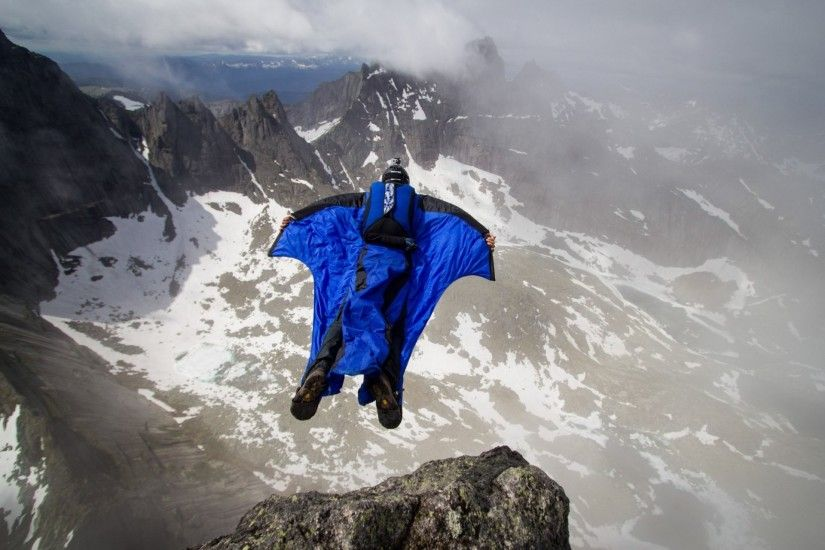 wingsuit pilot base jumping base jumper mountain rock clouds trailers  parachute extreme sports