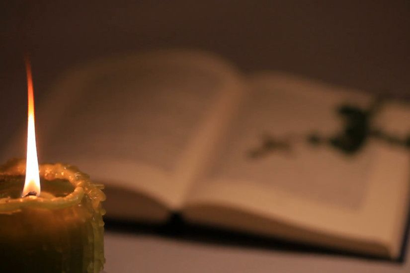 An open blurry bible with a rosary on background and a lighted candle on  foreground Stock Video Footage - VideoBlocks