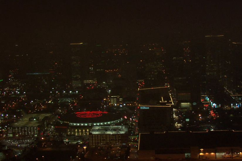 Houston Skyline Nighttime. A beautiful aerial view of the Houston skyline  at night. Towering buildings light up the background with the Toyota Center  at the ...