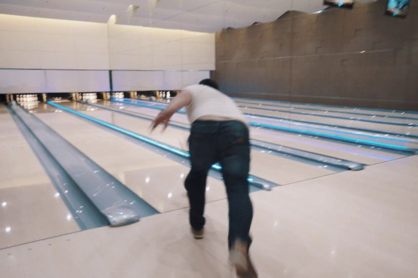 Man in white shirt and jeans throws black bowling ball in bright skittle  ground with large wall mirror, flashing colorful lights Stock Video Footage  - ...