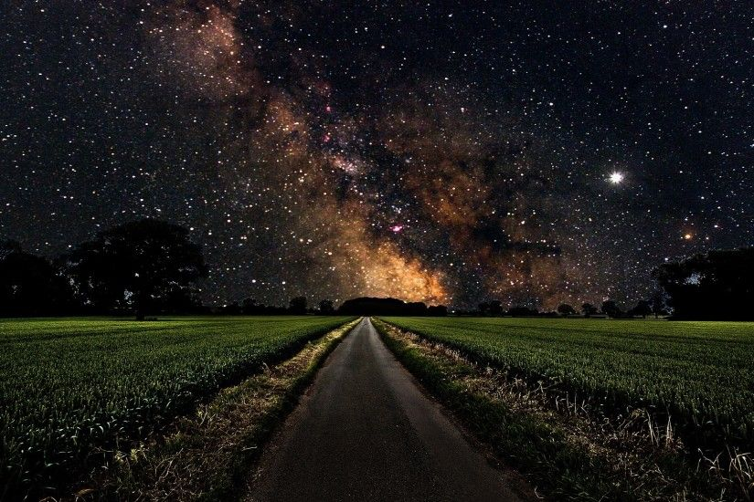 Milky Way over a green field wallpaper