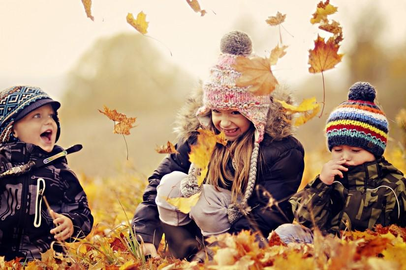 Kids Playing with Autumn Leaves Wallpaper