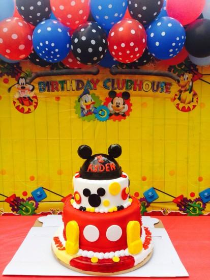 Cake table with a beautiful background for a Mickey mouse party.
