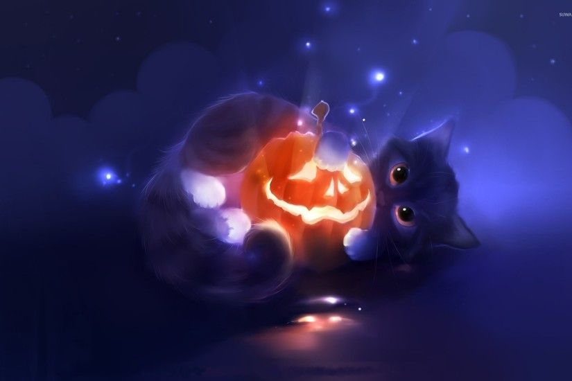 Cute kitten holding a happy Jack-o'-lantern wallpaper