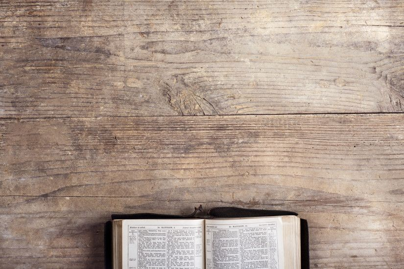 Bible on a wooden desk - Opened bible on a wooden desk background.