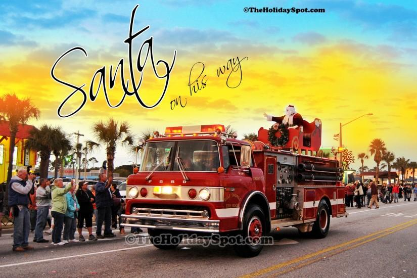 Christmas wallpaper of Santa coming to town on a firefighter truck.