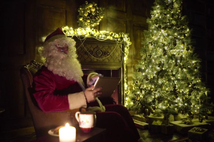 Santa Claus working, shopping gifts on line with tablet, christmas tree  with lights and decorated fireplace in background Stock Video Footage -  VideoBlocks