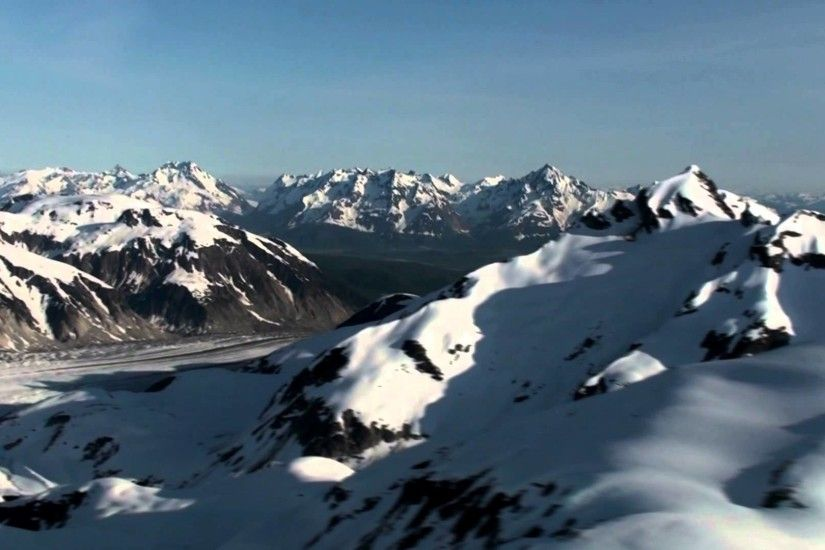 Aerial view of the snow covered Coast Mountains with blue sky in the  background, Alaska.
