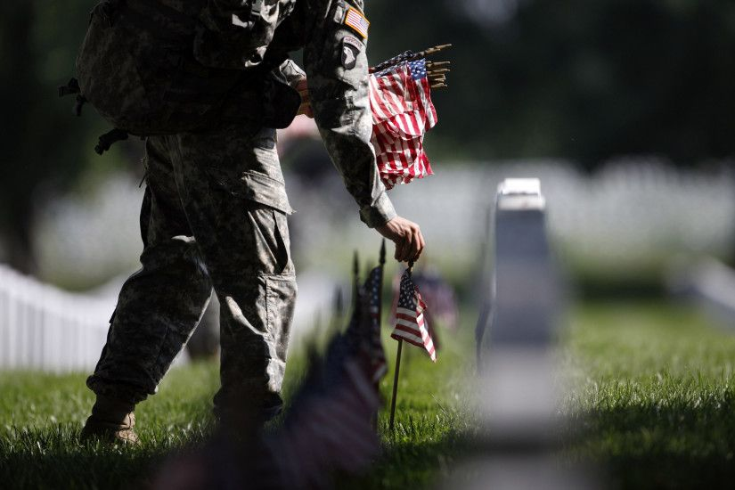 A member of the U.S. Army Old Guard places a flag at one of the over