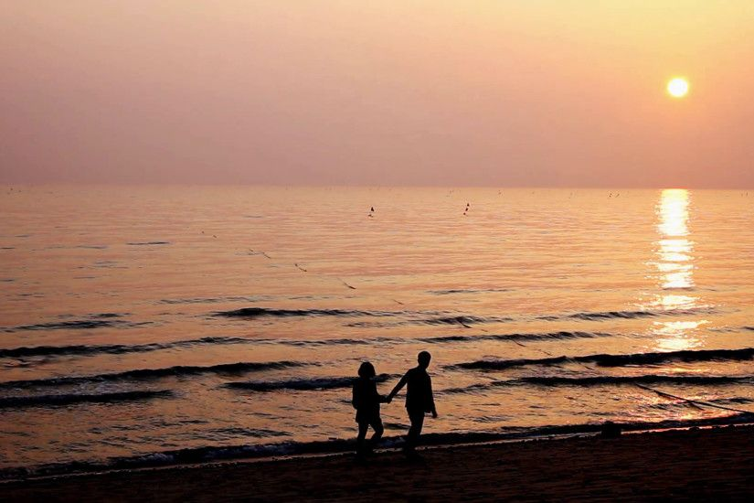 Silhouette of teenage couple holding hands and embracing on the beautiful sunset  beach