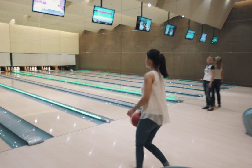 Girl in white shirt and jeans throws red bowling ball in bright skittle  ground with large wall mirror, flashing colorful lights Stock Video Footage  - ...
