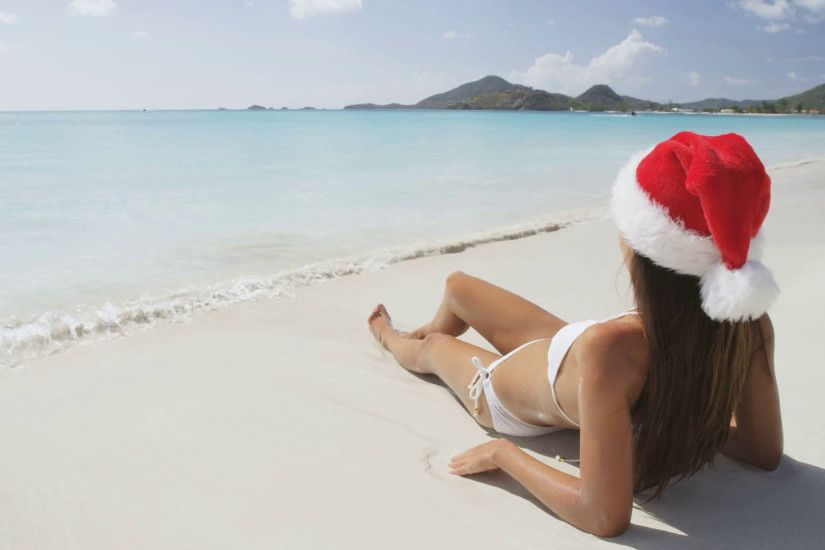 Christmas beach vacation woman wearing santa hat and bikini on holidays  travel vacation getaway travel relaxing on tropical beach lying in the sand.