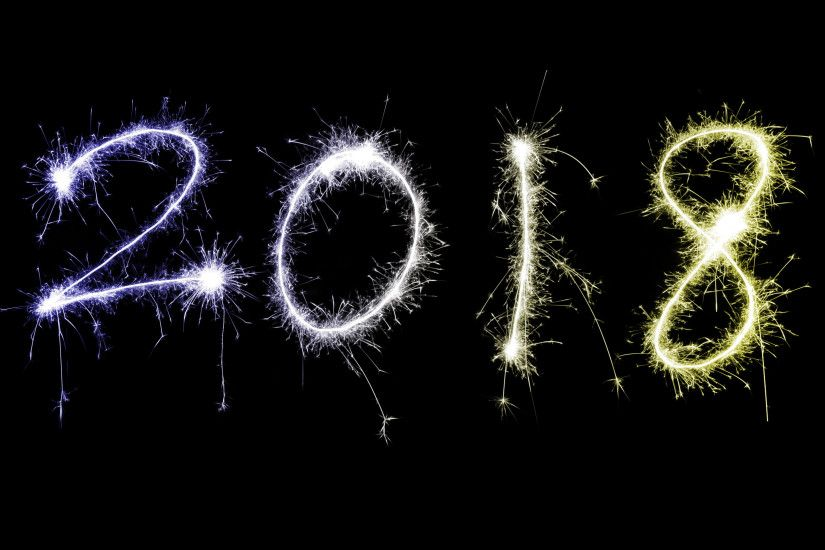 Fiery colorful multicolored 2018 New Year date with sparkling trails over a  black background with copy