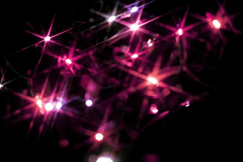 Christmas background of colourful vivid pink starburst lights scattered in  the darkness sparkling and glowing for