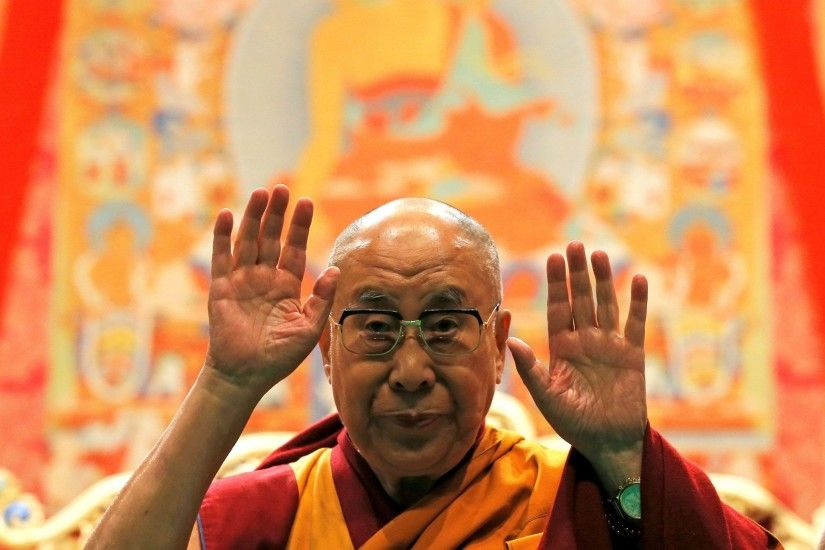 Tibet's exiled spiritual leader the Dalai Lama gestures as he arrives to  give a public religious
