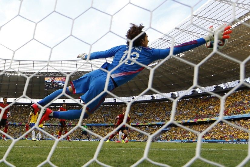 ... Mexico goalkeeper Guillermo Ochoa makes a save on a shot by Brazil's  Neymar during Tuesday's match