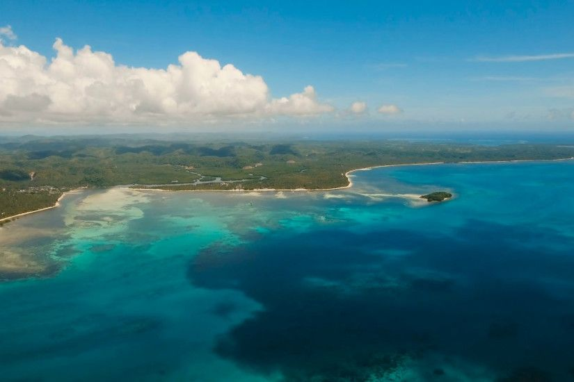 Coastline of the tropical island Siargao with the mountains and the  rainforest on a background of ocean with big waves. Aerial view: sea and  the tropical ...