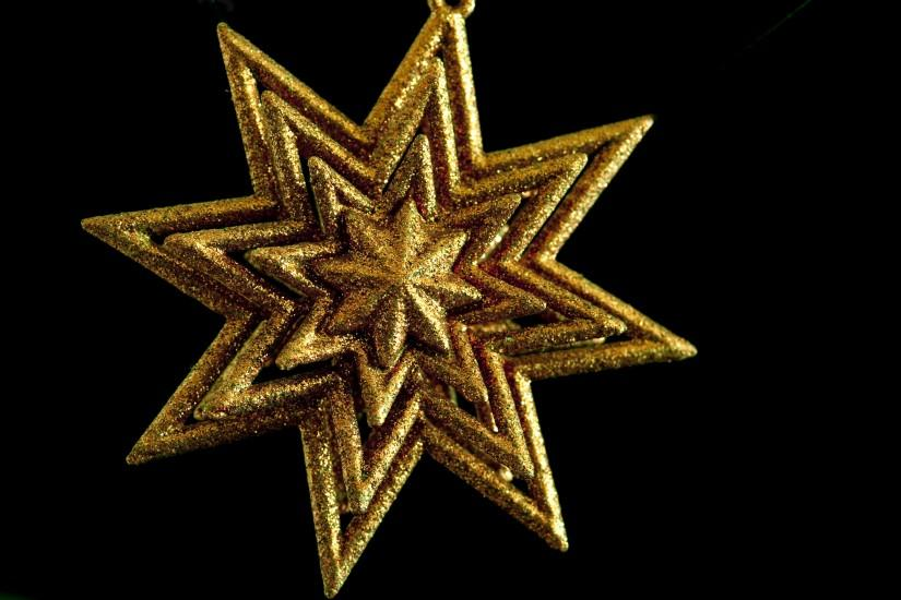 a gold coloured glittering christmas star on a black background