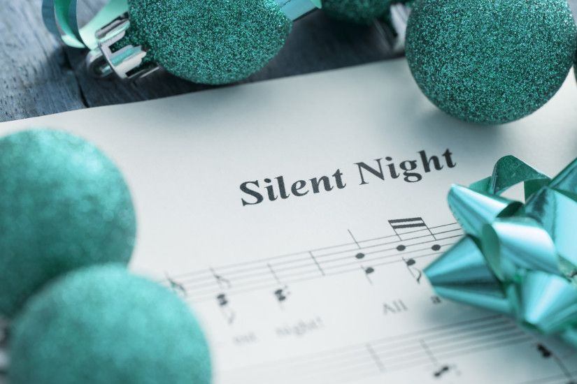Decorative Christmas carols music background with the score for Silent  Night surrounded by green glitter baubles