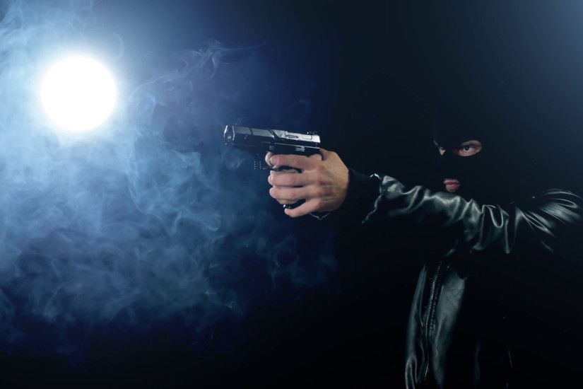 masked criminal gangster holding gun black background Stock Video Footage -  VideoBlocks
