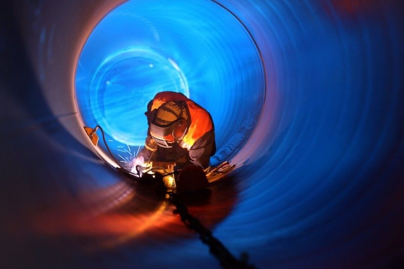 welder experienced mounting of the pipeline performs connection docking  metal real estate light sparks beautiful background
